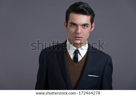 Retro fifties business fashion man with dark grease hair. Wearing dark blue suit and tie. Studio shot against grey.