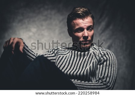 Retro fifties cool rebellion fashion man wearing striped woolen sweater. Gray wall.