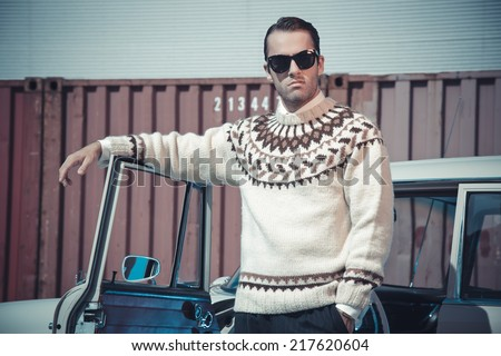 Retro fifties fashion man with woolen sweater and sunglasses standing against vintage car. - stock photo