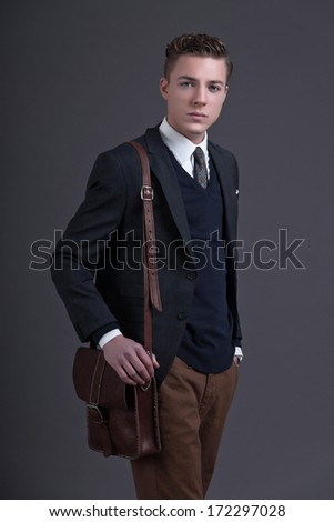 Retro fifties fashion young businessman wearing dark suit and tie. Holding a brown leather bag. Studio shot against grey.