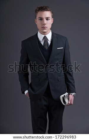 Retro fifties fashion young businessman wearing dark suit and tie. Holding a newspaper. Studio shot against grey.