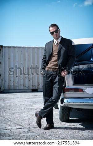 Retro fifties mafia fashion man standing next to open trunk of vintage car. - stock photo
