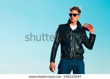 Retro fifties rockabilly man with black jacket listens to portable radio. Outdoor. Blue sky.