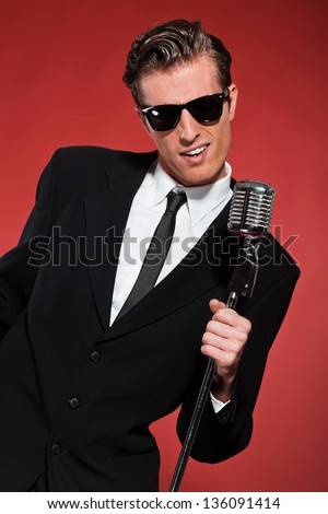 Retro fifties singer with vintage microphone and sunglasses. Studio shot. - stock photo