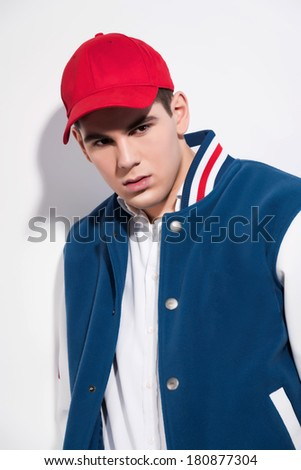 Retro fifties sportive fashion man wearing blue baseball jacket and red cap. Studio shot against white. - stock photo