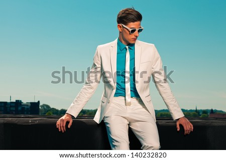 Retro fifties summer fashion man with white suit and sunglasses. On rooftop. Blue sky. - stock photo