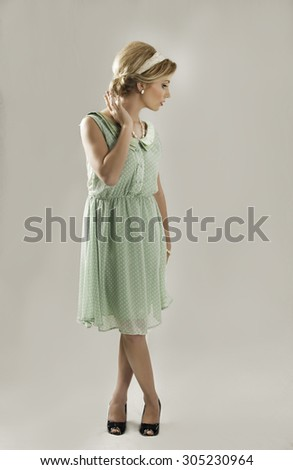 Retro fifties woman in green dress with black shoes looking to the side. - stock photo