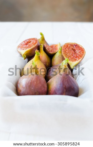 Retro Figs in a tray with painted backdrop in background, selective focus - stock photo