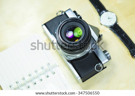 Retro Film Camera, watch, notebook isolated on wood table.  - stock photo