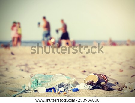Retro filtered garbage on a beach left by tourist, environmental pollution concept picture, Baltic Sea, Poland. - stock photo