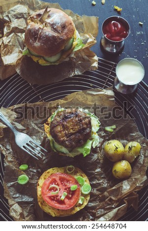 Retro Filtered Image: Homemade Juicy Pork Burger, a Veggie One with a Flag Topper and Buttered Baby Potatoes with Dill - stock photo