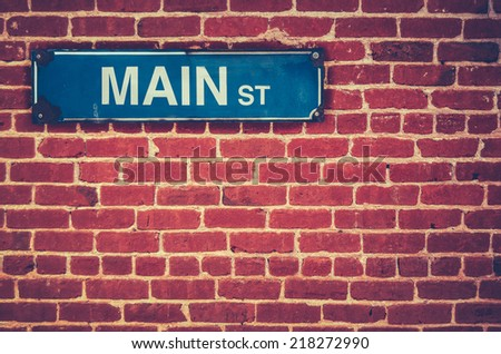 Retro Filtered Photo Of A Main Street Sign On A Red Brick Wall - stock photo