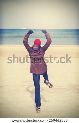 Retro filtered photo of woman jumping on beach, winter active lifestyle concept. - stock photo