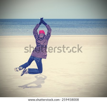 Retro filtered photo of woman jumping on beach, winter active lifestyle concept, space for text. - stock photo