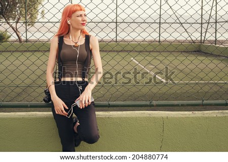 retro filtered photograph of a hipster girl with a mobile phone - stock photo