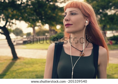 retro filtered photograph of a hipster girl with headphones - stock photo