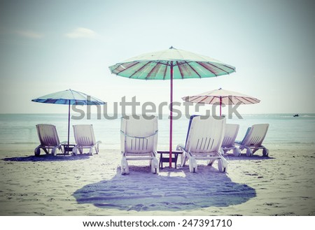 Retro filtered picture of beach chairs and umbrellas. Concept of relaxation and holidays.  - stock photo