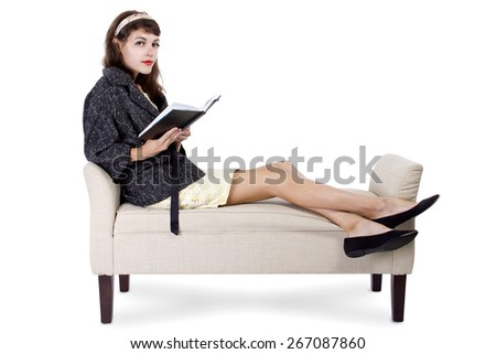 Retro girl sitting on  chaise lounge reading a book on a white background - stock photo