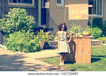 retro girl wearing sunglasses with lemonade stand - stock photo