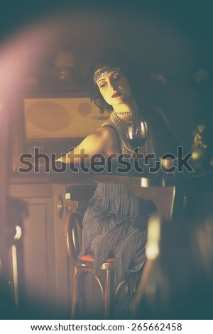 Retro girl with glasses of red wine in restaurant.Fashion,retro, vintage, tones. Antique picture with scratches and film grain. - stock photo