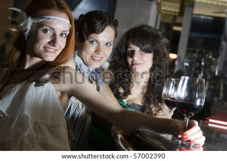 Retro girlfriends at bar with wineglasses - stock photo