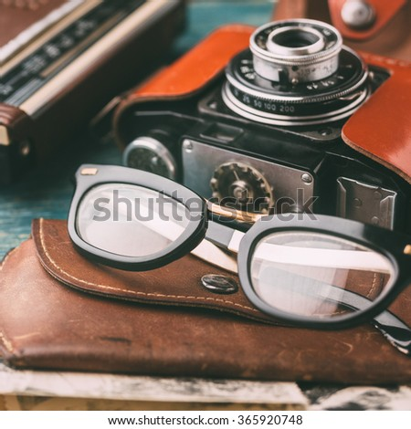 Retro glasses and Old retro camera close up, vintage toned