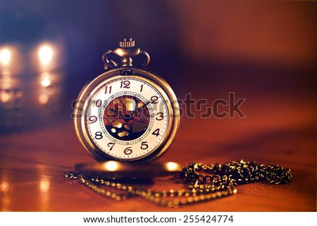 retro gold pocket watch in beautiful lighting candle on brown background - stock photo