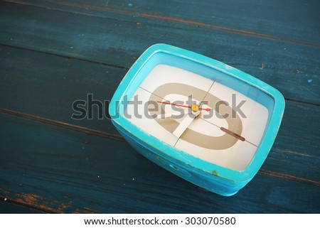 Retro green alarm clock on the wooden table. Toned image. - stock photo