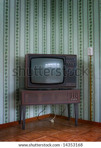 Retro grunge tv against wallpaper wall. - stock photo