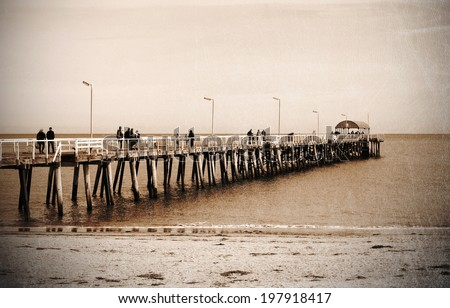 Retro grunge vintage style sepia people on jetty pier boardwalk over sandy beach.