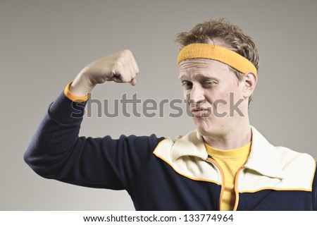 Retro Gym Coach Flexing His Pathetic Muscles - stock photo