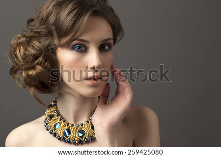 Retro hairstyle. Beautiful Brunette Woman. Fashion portrait with jewerly.On gray background.Hand near her neck. - stock photo