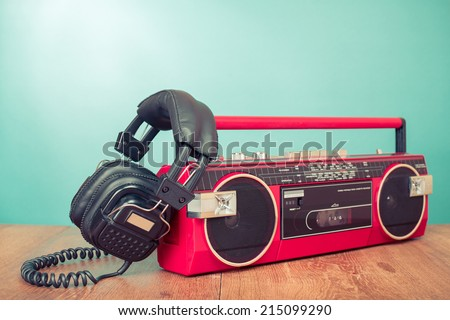 Retro headphones and red radio tape recorder on table - stock photo
