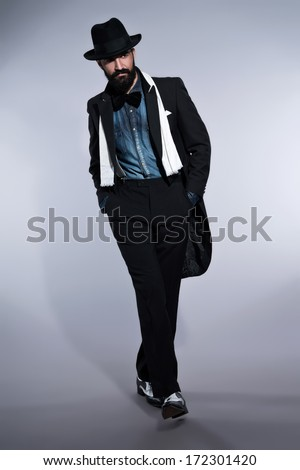 Retro hipster 1900 fashion man in suit with black hair and beard. Wearing blue jeans shirt plus hat. Studio shot against grey.