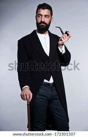 Retro hipster 1900 fashion man with black hair and beard. Smoking pipe. Studio shot against grey.