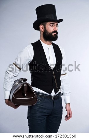Retro hipster 1900 fashion man with black hair and beard. Wearing black hat. Holding vintage bag. Studio shot against grey.
