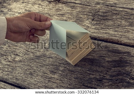 Retro image od male hand covering a house miniature made of wooden pegs with a paper roof. Conceptual of real estate, architecture or design and home ownership.  - stock photo