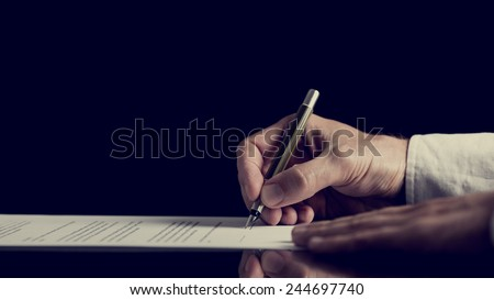 Retro image of a man signing a contract over dark background. - stock photo