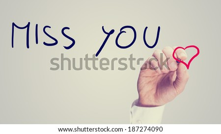 Retro image of a man writing a romantic - Miss You - message on a virtual screen with a red heart as he sends a greeting to his loved one or sweetheart, with copyspace.