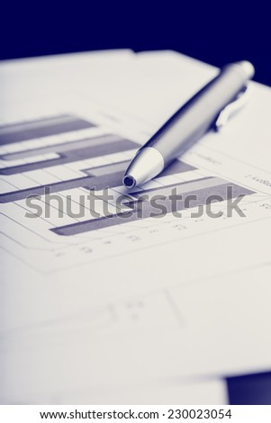 Retro image of ballpoint pen lying on a bar graph in a business strategy concept. - stock photo