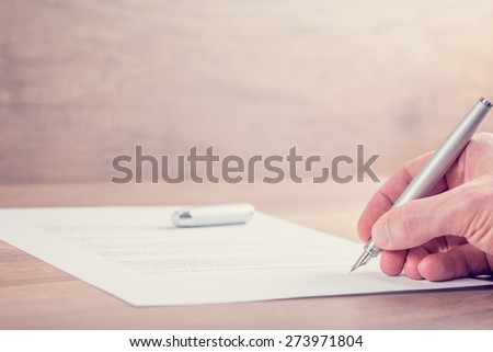 Retro image of businessman hand signing contract or other important documents on a rustic wooden desk. - stock photo