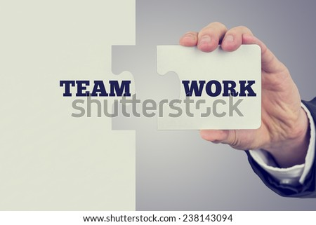 Retro image of businessman holding two matching puzzle pieces with the word - Teamwork - spread over them. - stock photo