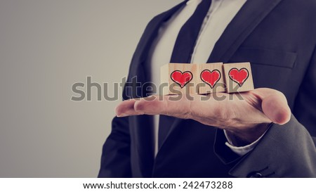 Retro image of businessman holding wooden alphabet blocks with a hand-drawn red heart balanced in the palm of his hand in a tender tribute to a loved one, or for an anniversary or Valentines Day. - stock photo