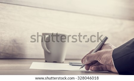 Retro image of businessman signing contract or authorizing important documents at his wooden desk wit cup of coffee on it. - stock photo