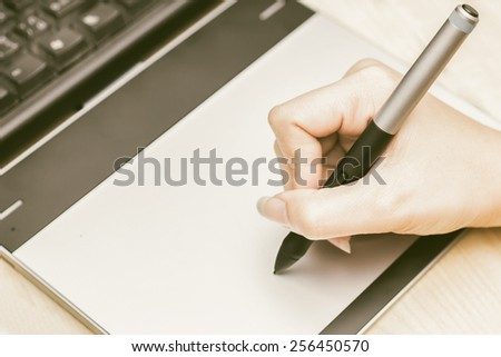 Retro image of female hand of a designer drawing with the stylus on a grey graphics tablet - stock photo