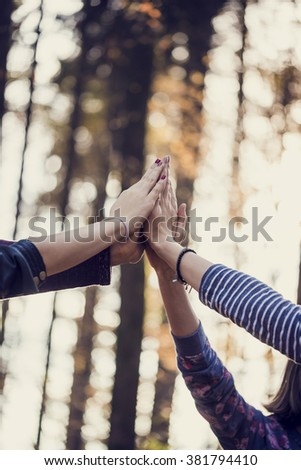 Retro image of four female hand joining high up in the air outside in woodland. Conceptual of teamwork and friendship. - stock photo
