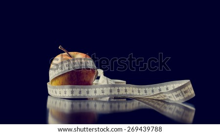 Retro image of fresh apple wrapped with a white measuring tape, with reflection and copy space on dark blue, concept of diet and healthy nutrition. - stock photo
