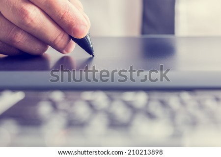 Retro image of male hand of a designer drawing with the stylus on a grey graphics tablet, close-up. - stock photo