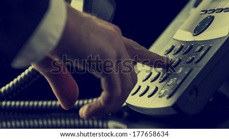 Retro image of man in a suit dialing out on a landline telephone with a close up view of his finger pressing a number button on the keypad as he makes a call. - stock photo