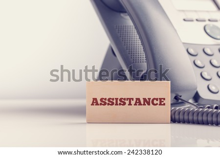 Retro image of support concept with a small wooden sign saying - Assistance - standing alongside a telephone instrument with copyspace. - stock photo